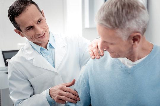 Positive delighted doctor doing massage on shoulder