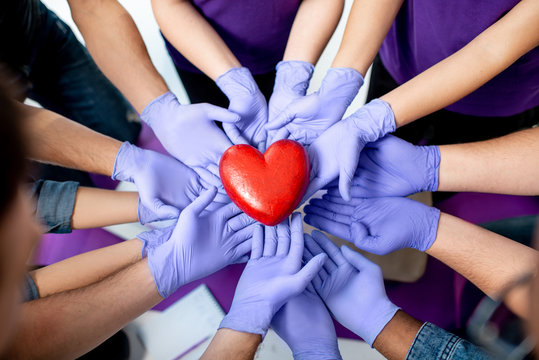 Group of people holding with hands in medical gloves red heart model. Close-up view. Healthy heart concept.