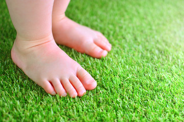 Artificial grass background. Tender foots of a baby on a green artificial turf floor.