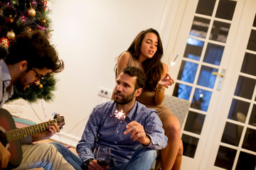 Couple congratulates New Year with sprayers while young man playing guitar