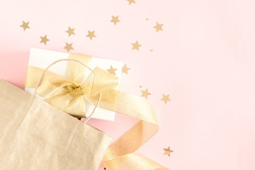 Paper bag and gift with gold ribbon on pastel pink background. Christmas, New Year, birthday. Flat lay, top view, copy space