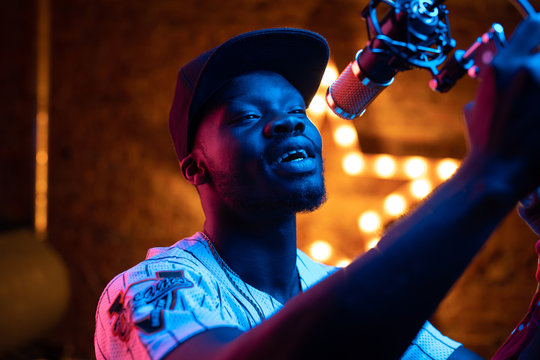 Man with beard and mustaches in baseball cap and t-shirt sing in microphone. Pink and blue neon light, star on background