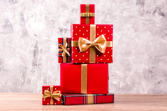 Christmas preparation concept. Stack of different colorful presents for every family membet. Pile of gifts in bright festive wrapping. Close up, copy space grunged concrete wall background.