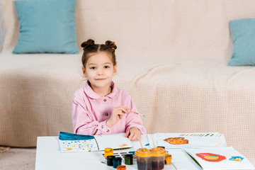 cute happy child painting pictures and smiling at camera