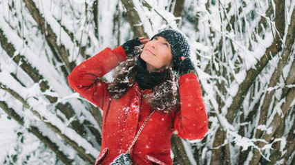 Young woman in red down jacket and black hat looking up for snow flakes while outside is snowing