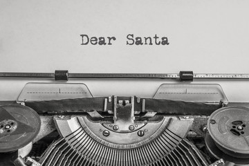 Dear Santa text typed on a vintage typewriter, black ink on old paper. A letter to Santa Claus with wishes for gifts for the New Year and Christmas
