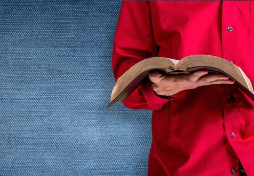 Man hand holding holy bible on background