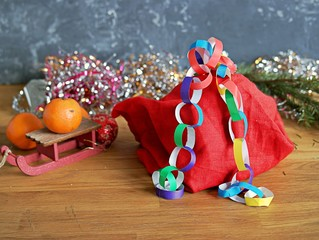 Garland of handmade colored paper to decorate a Christmas tree or room in the New Year's style. Children's DIY. Merry Christmas and New Year concept.