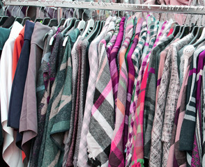 Coat shirts and many used clothes hanging in the stall