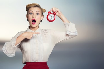 Shocked woman with alarm clock on blurred interior background