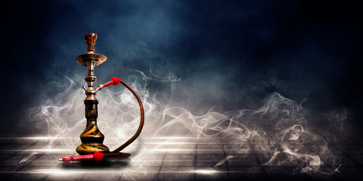 Smoking a hookah on a dark concrete field, in clouds of smoke and neon light