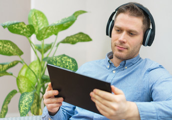 Man watching movie on tablet pc with wireless headphones.