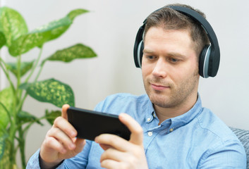 Man using mobile phone with wireless headphones.