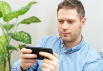 Handsome unshaved man playing game on mobile phone.