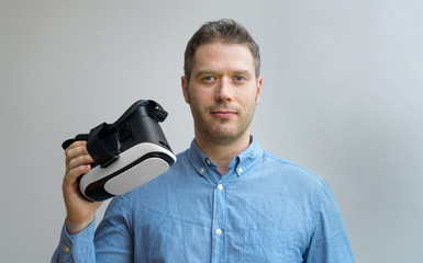 Handsome man holding virtual reality goggles. Space for your text.