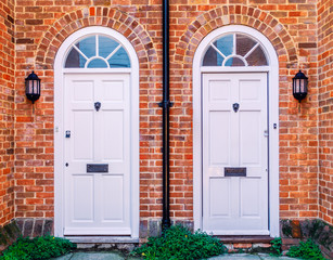 Two white wood residential front doors, with a drain pipe down the middle. The walls are red brick there are lunette arches over the doors and metal lion door knockers