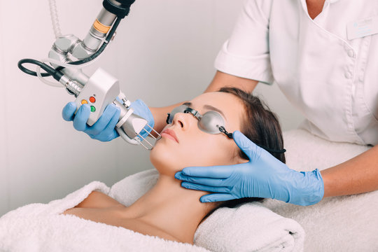 woman getting laser facial treatment, aesthetic surgery,