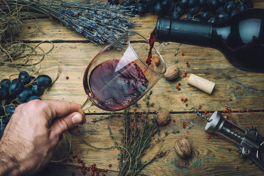 Wine maker pouring red wine (bio) for tasting. Red wine tasting (bio wine) in a wine glass with grapes, nuts and herbs on the background of the old wooden table. Table setting.