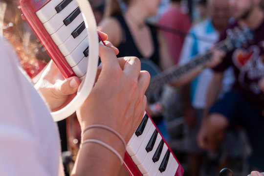 Crop person playing melodica
