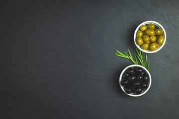 Set of green and black olives on plate and rosemary