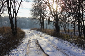 Beautiful rural dirt road under the snow, track with frozen puddles of water on the edge of the forest - country landscape, travel, sun in the back light