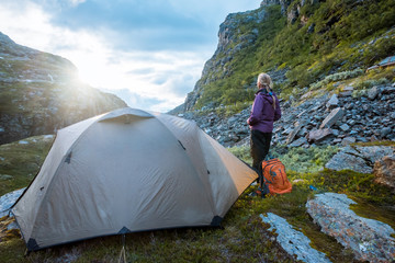 tourist tent and woman in mountains sunset Norway