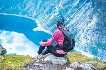 Young woman with backpack on top of fjord Norway