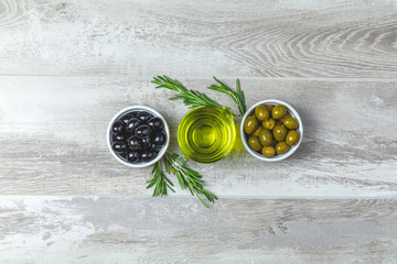 Set of black and green olives on plates, olive oil and rosemary