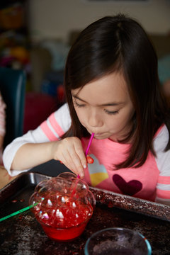 Girl blowing bubbles in dye for crafting project