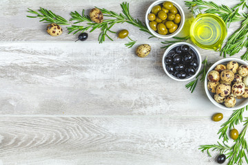 Set of black and green olives, quail eggs on plates, olive oil and rosemary