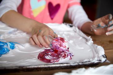 Girl swirls an easter egg in purple dye and shaving cream