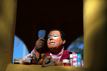 Salvadorean clown applies makeup as he participates during Salvadoran Clown Day celebrations in Santa Tecla