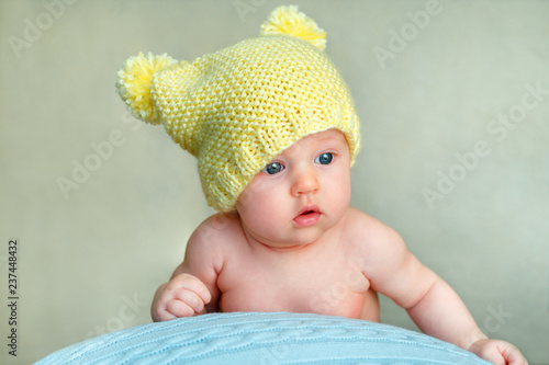 0394da59e619 Portrait of a cute newborn baby girl in yellow knitted hat posing on ...