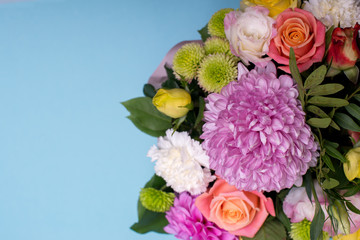beautiful floral arrangement, pink and yellow rose, pink eustoma, green and pink chrysanthemum, white carnation, pink dahlia on a blue, turquoise background with space for text.