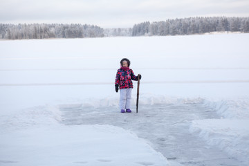 Young girl with crowbar in hand standing near cleared ice on lake for making ice-hole
