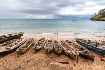 Sao Tome, traditional wooden dugouts on the beach in a fishermen's village, a dog in the sea