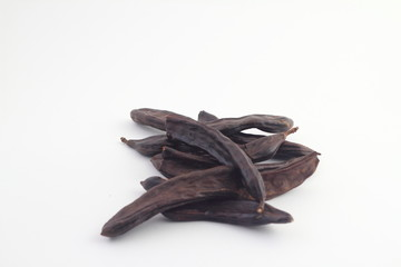 Carob on white background. Organic carob pods with seeds