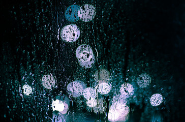 glare of the night city through the window in the drops of rain