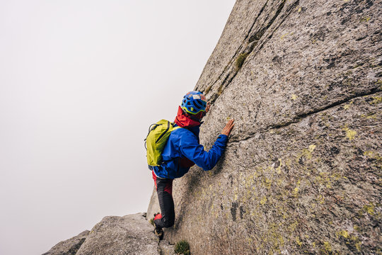 A solo climber ascending a steep rock face. Dangerous climb in a big wall without rope or protection. Free solo.