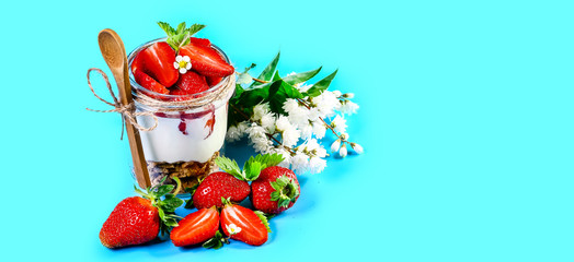 Summer dessert fresh strawberry, cream cheese and strawberry jam on glasses isolated on a blue background. Copy space