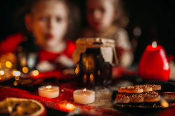 Children at the festive table. Bank of jam, candles and cookies on the table