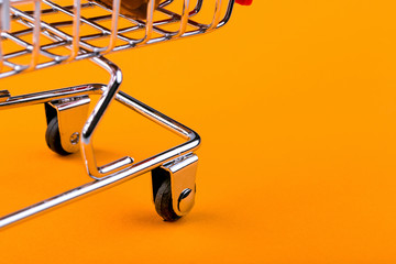 shopping trolley on orange background, shopaholic concept Wall mural