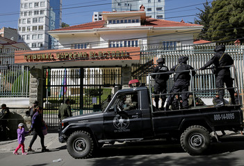 Security forces stand guard in front of the Supreme Electoral Court during protests against Bolivia's President Evo Morales bid for re-election in 2019, in La Paz