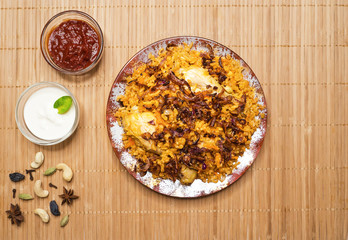 Delicious spicy chicken Biryani in a plate  on a bamboo napkin, Indian or Pakistani food.