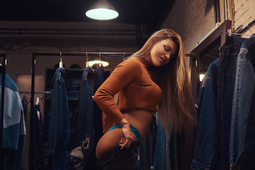 A sexy girl seductively pulling up pants in a fitting room of a clothing store