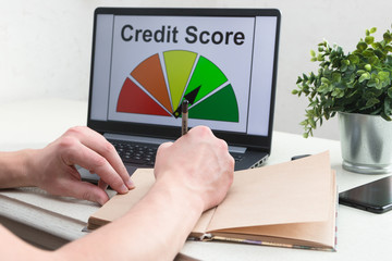A man calculates his finances and analyzes the credit history, compiles a credit report on a computer. Credit score. Laptop. Technology.