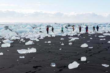 View of the tourists photographing ice floes in the beach in Jökulsárlón, Icelands
