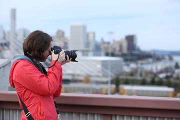 Side view of Woman in orange red coat holding camera to eye  in urban city setting
