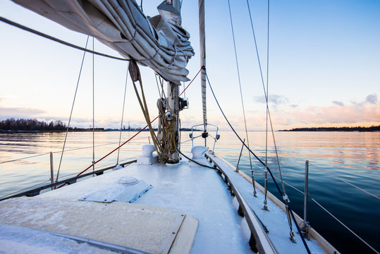 Colorful winter sunset. White yacht sailing, a view from the deck to the bow and sails. Baltic sea, Latvia