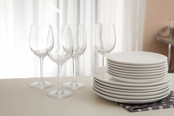 Stack of clean dishes and glasses on table in kitchen
